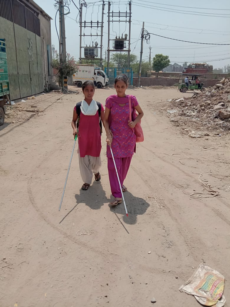 BLIND GIRLS MOVING INDEPENDENTLY WITH THE SUPPORT OF WHITE CAIN